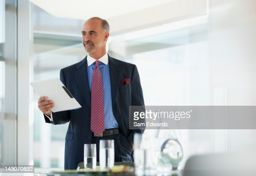 Businessman holding folder in office : Stock Photo