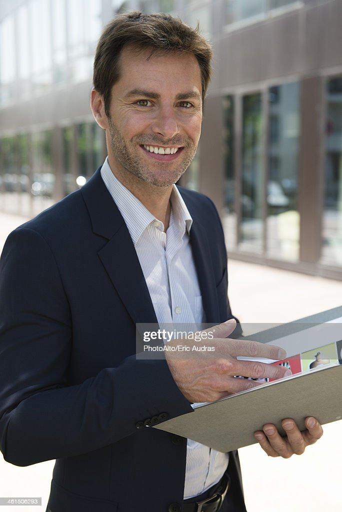 Businessman holding folder, portrait