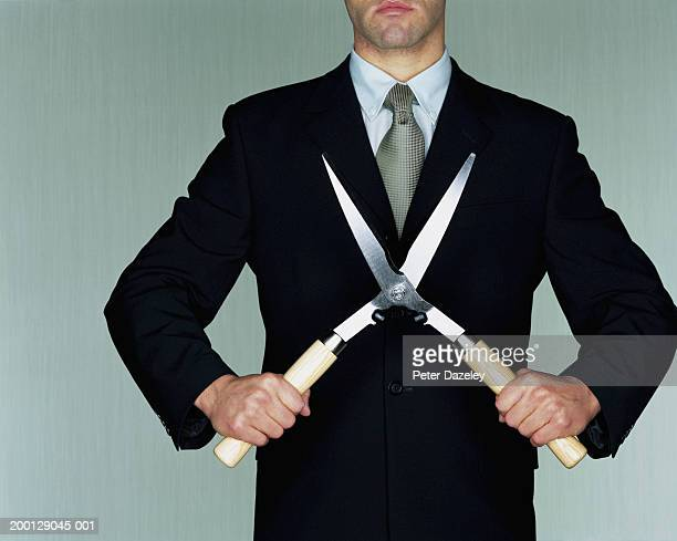 Businessman holding garden shears, mid section