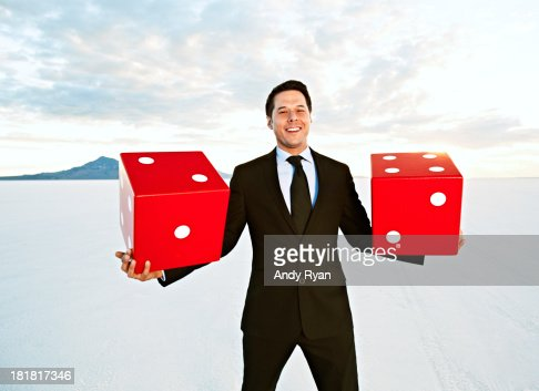 Businessman holding giant dice, smiling. : Stock Photo