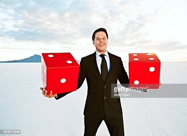 Businessman holding giant dice, smiling.