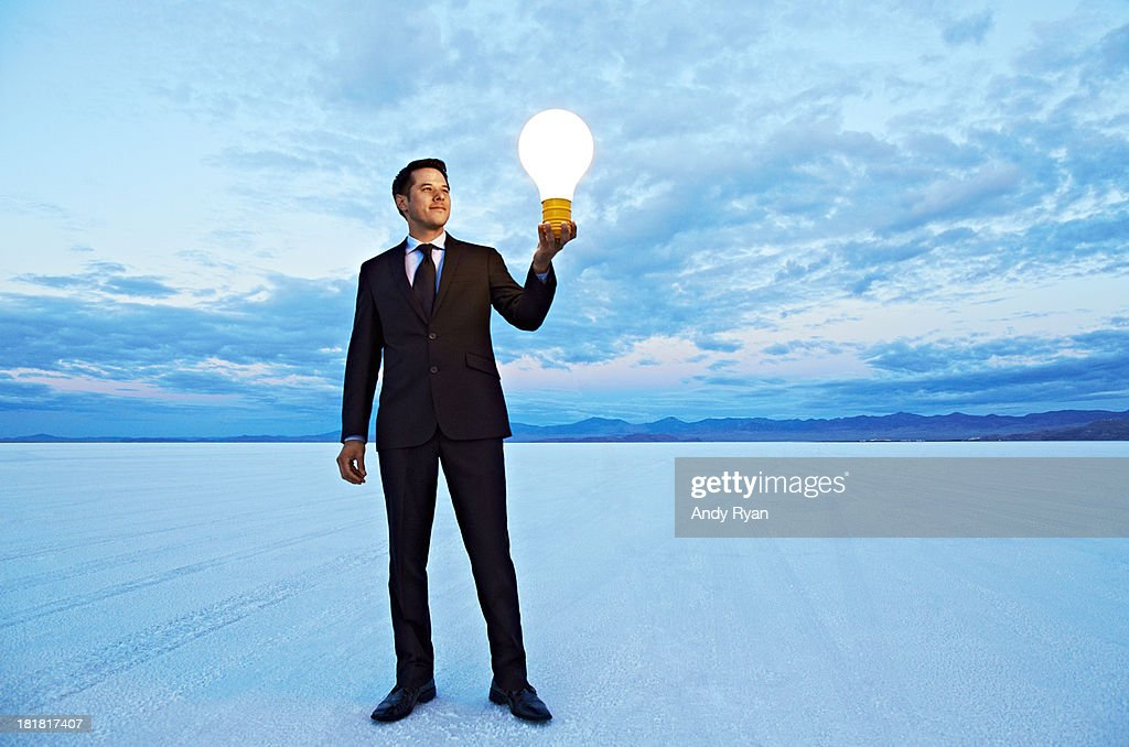 Businessman holding giant lightbulb in desert. : Stock Photo