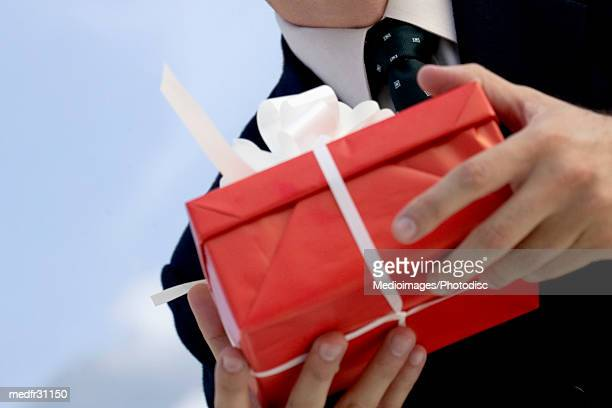 Businessman holding gift in red box with white ribbon outdoors, close-up