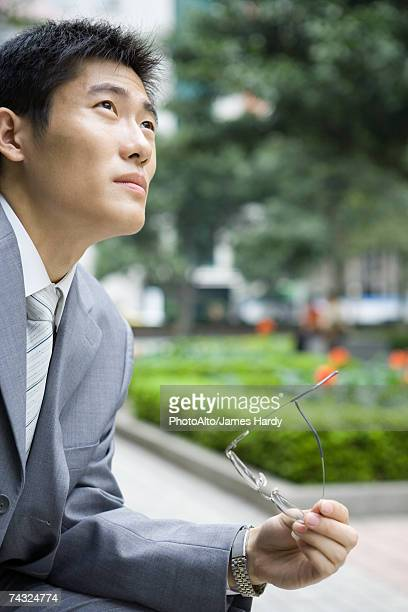 Businessman holding glasses, looking up