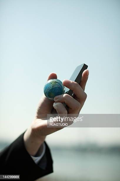 businessman holding globe ball and mobile phone