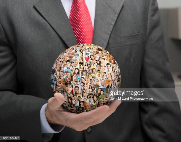 Businessman holding globe collage of business people's faces