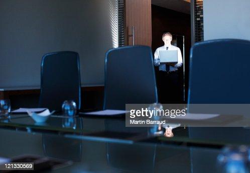 Empresario sosteniendo port til en oficina brillante por for Oficina portatil