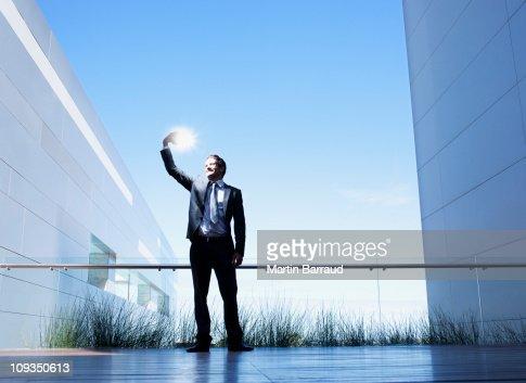 Businessman holding glowing light on balcony : Stock Photo