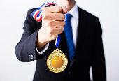 businessman holding gold medals