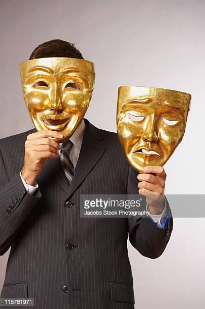 Businessman Holding Happy and Sad Masks