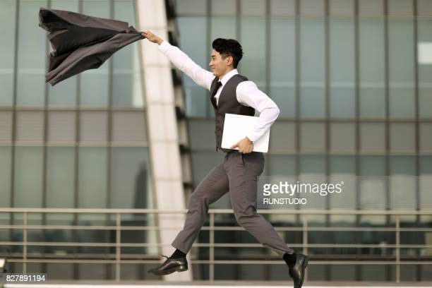 businessman holding his coat and jumping