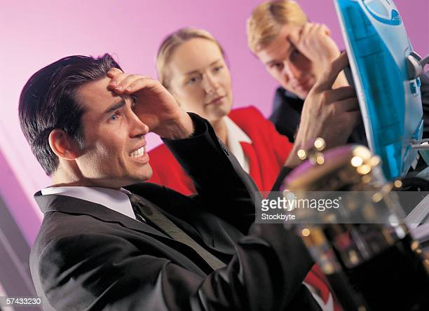 businessman holding his head sitting in front of a computer with his colleagues