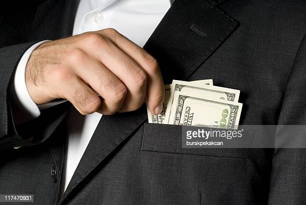Uomo d'affari con banconote da cento dollari nella tasca della giacca, close-up