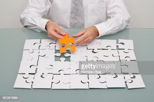 Businessman holding jigsaw piece. : Stock Photo