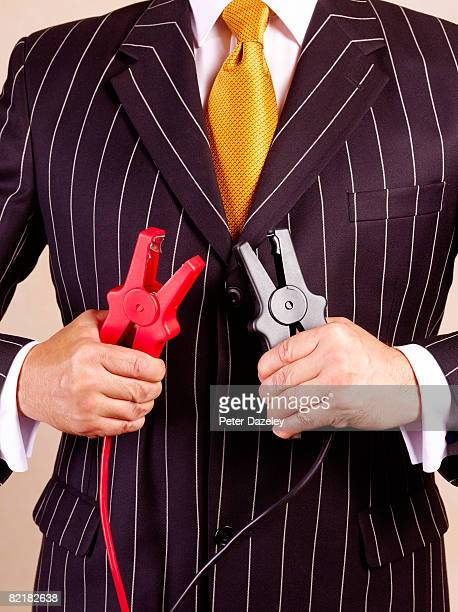 Businessman holding jump leads in pinstripe suit
