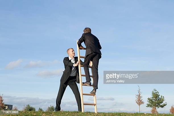 Businessman holding ladder for colleague