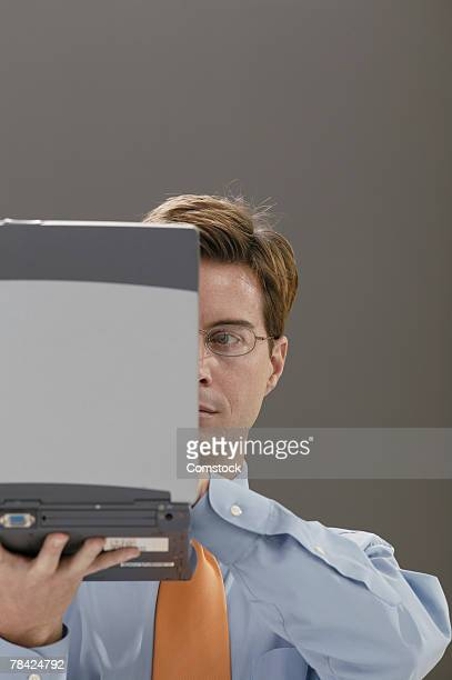 Businessman holding laptop in front of his face