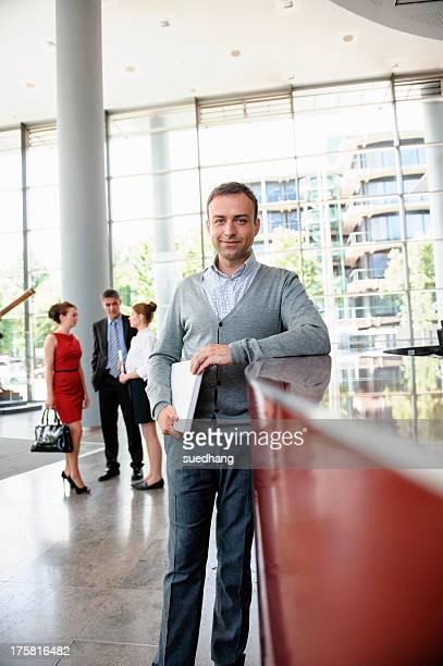 Businessman holding laptop leaning against reception desk