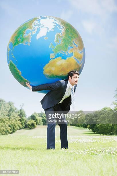 Businessman holding large ball on back