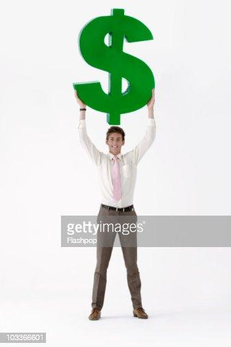 Businessman holding large dollar symbol : Stock Photo