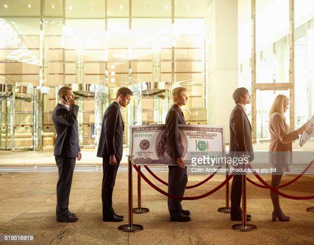 Businessman holding large hundred dollar bill in bank line