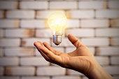 Businessman holding light bulb on her hands,idea concept.