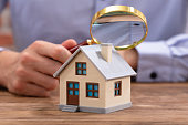 Close-up Of A Businessman's Hand Holding Magnifying Glass Over House Model Over Desk