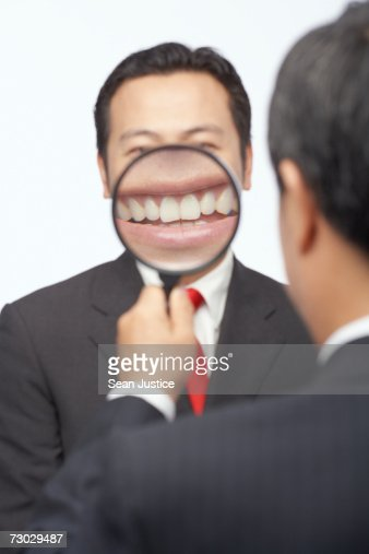 Businessman holding magnifying glass to mouth : Stock Photo