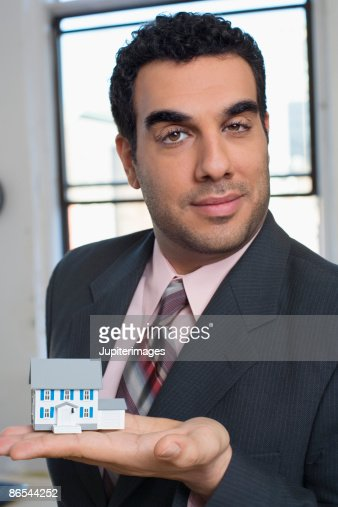 Businessman holding miniature house