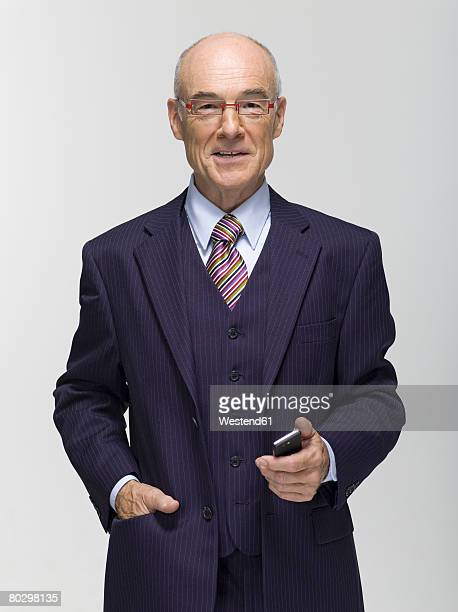 Businessman holding mobile phone, portrait, close-up