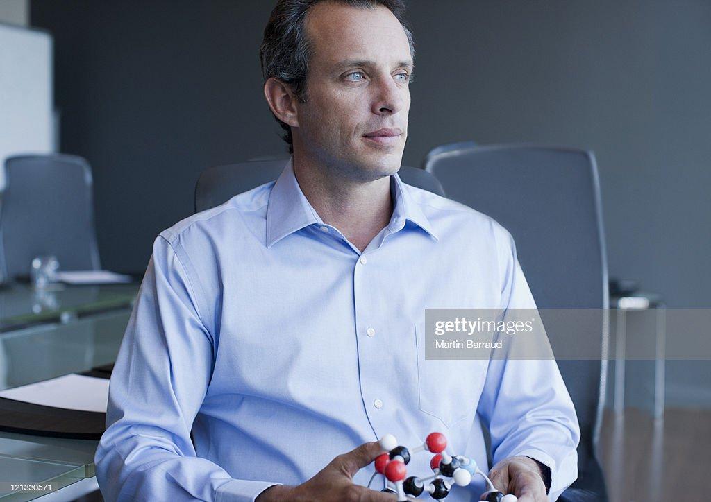 Businessman holding molecule model in office : Stock Photo