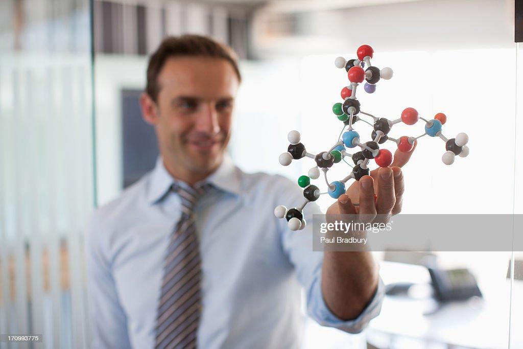 Businessman holding molecule model in office