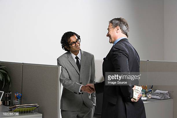 Businessman holding money behind his back