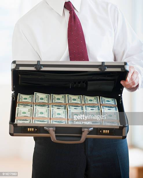 A businessman holding money in a briefcase