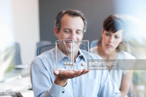 Geschäftsmann holding Newton's cradle im Büro