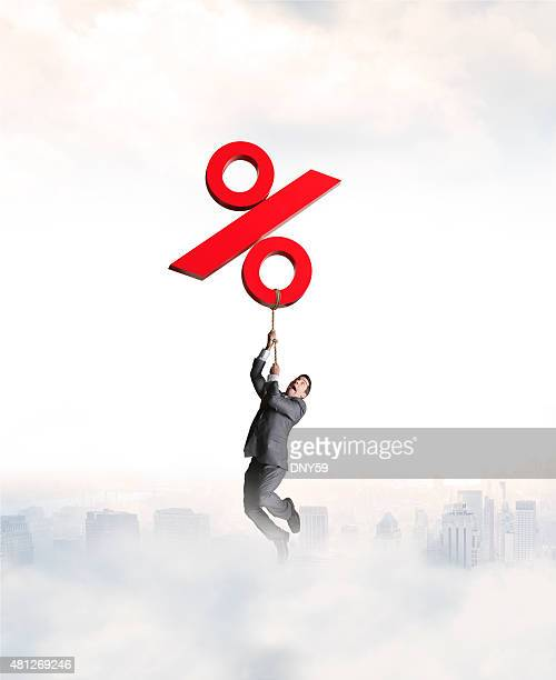 Businessman Holding On To Rising Red Percentage Sign