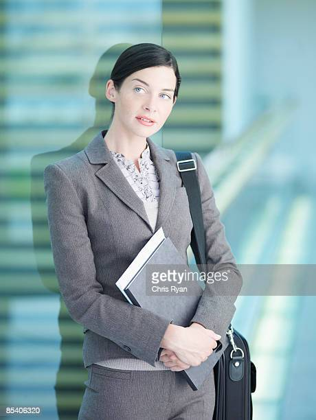 Businessman holding paperwork and briefcase