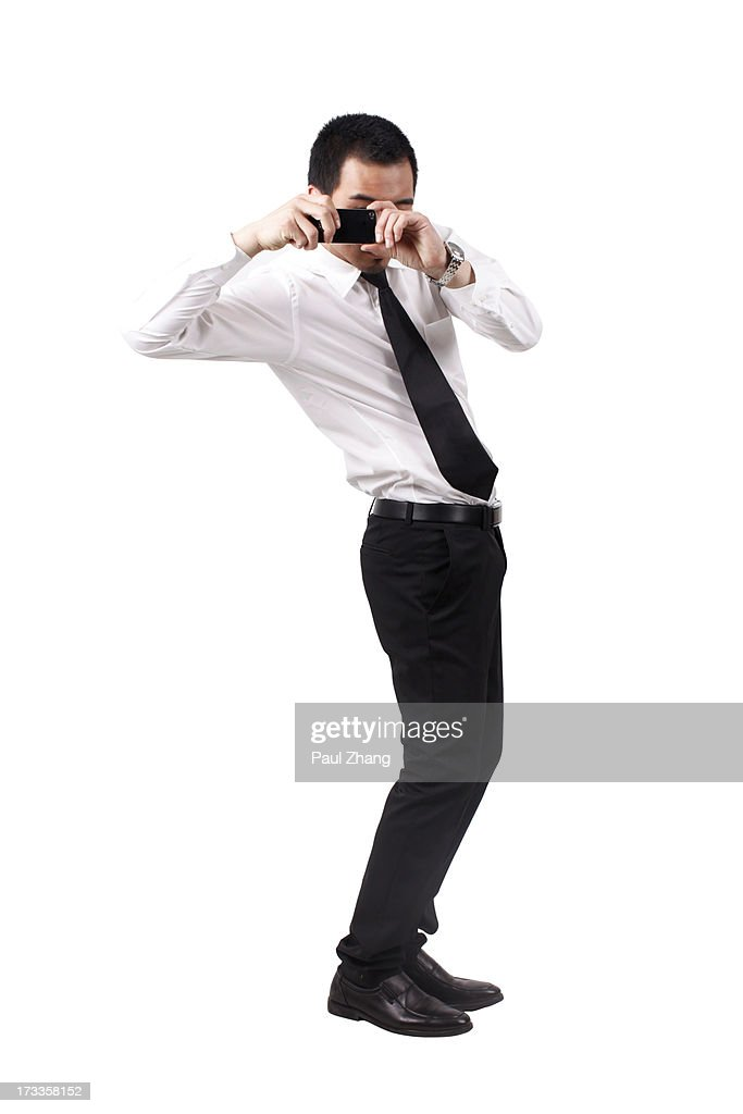 A businessman holding phone to take a photo : Stock Photo