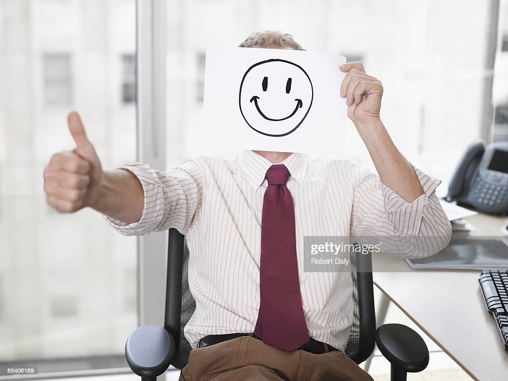 Businessman holding picture of happy face : Stock Photo