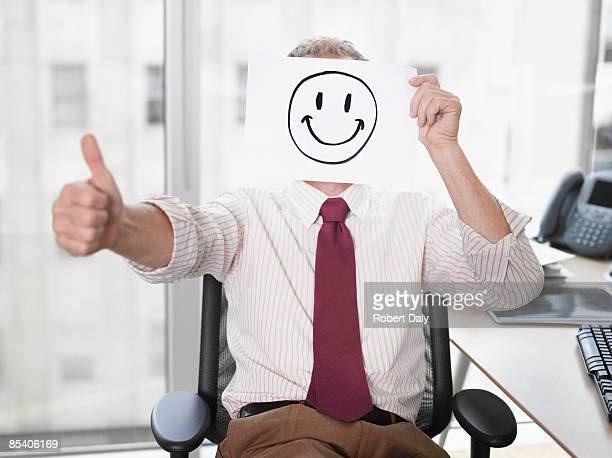 Businessman holding picture of happy face
