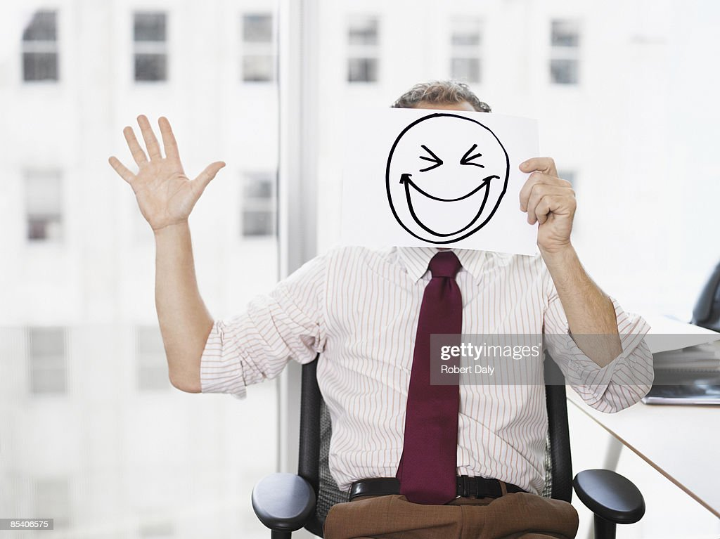 Businessman holding picture of laughing face : Stock Photo