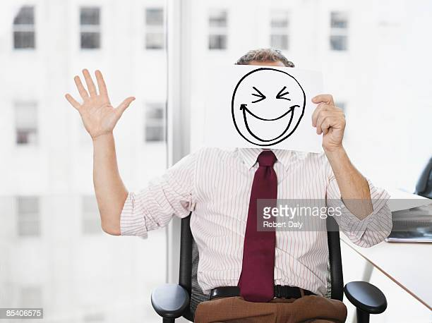 Businessman holding picture of laughing face