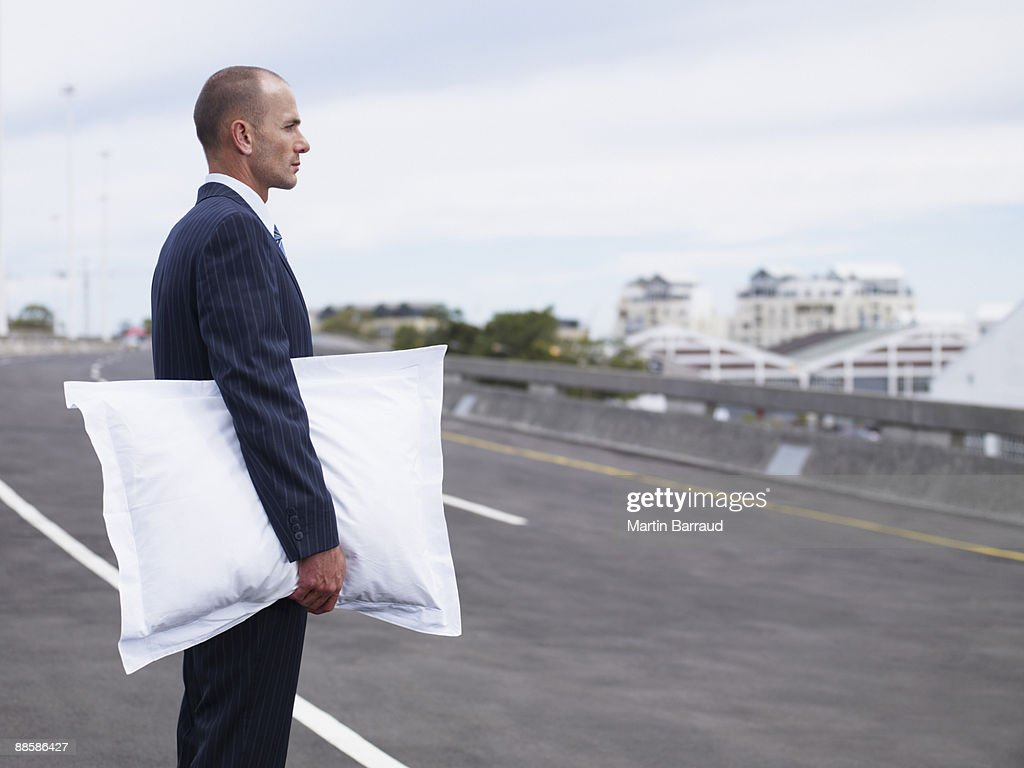 Businessman holding pillow in road : Stock Photo