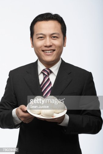 Businessman holding plate of steamed buns, portrait : Stock Photo