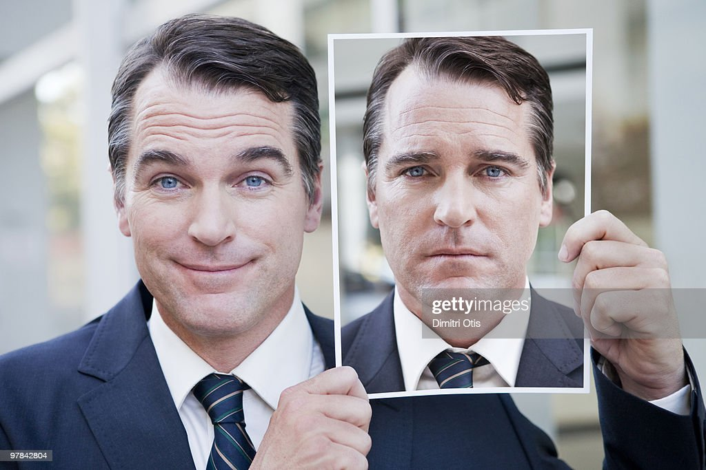 Businessman holding portrait of himself : Stock Photo