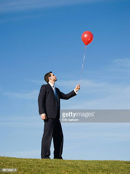 Businessman holding red balloon