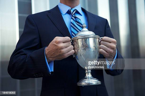 Businessman Holding Silver Trophy in front of Shiny Building