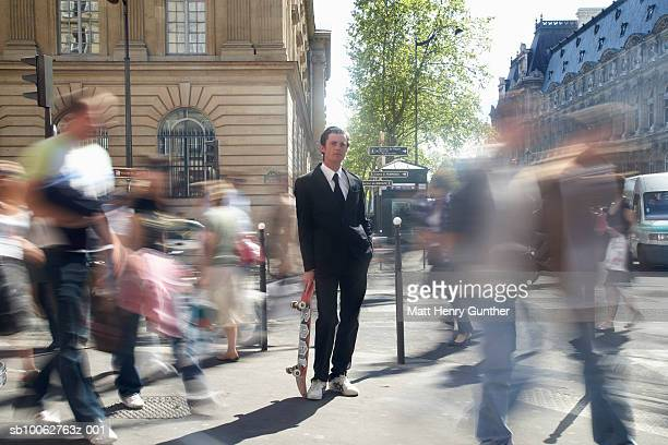 Businessman holding skateboard in streets, blurred motion