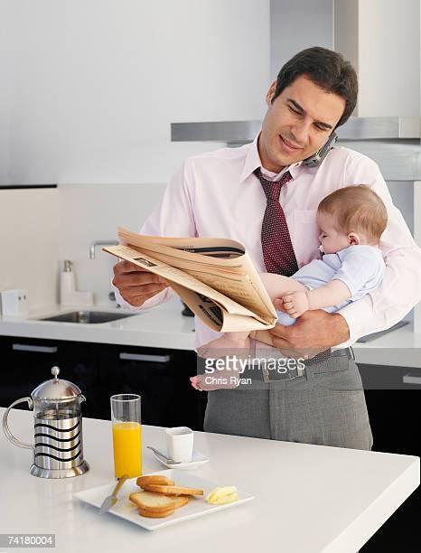 Homme d'affaires en tenant des bébés et journal parler sur Cellule
