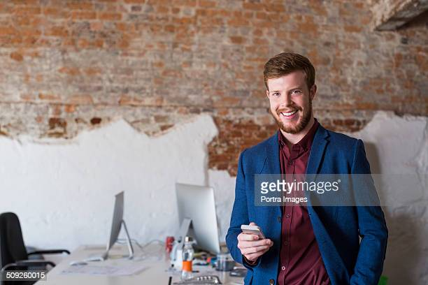 Businessman holding smart phone at creative office